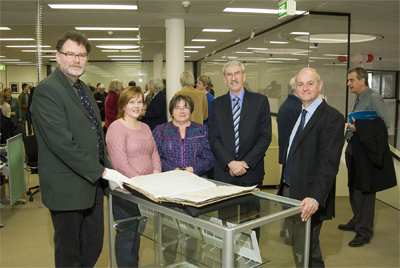 ArchivesACT's Elizabeth Estbergs (centre) with Minister John Hargreaves and first Director of Territory Records Office David Wardle (right) looking at Rates Book after launch