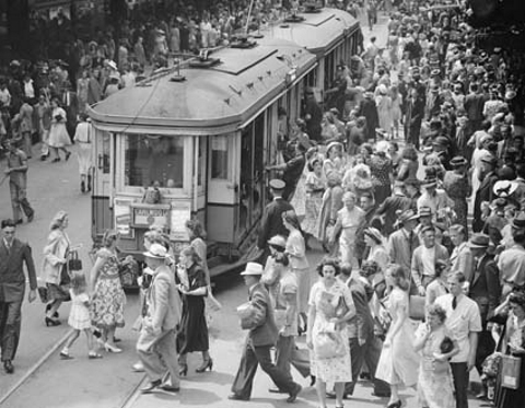 A busy crowd bustles around a tram on Pitt St in Sydney 1948