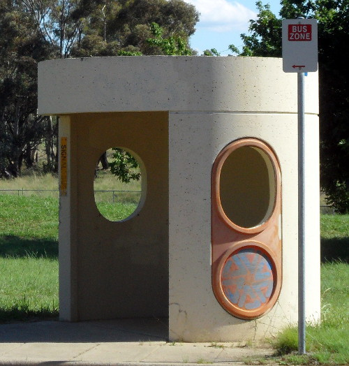 A concrete bus shelter without windowpanes due to vandalism